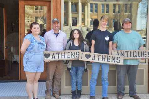 The students at the Exchange, part of the Athens City Schools system, meet in a repurposed space on the Square. From left, Caily McKinney, Dr. Chris Paysinger, Cheyenne Lopez, Colin Turner and Zack Kelley hold up wood plank signs they made at school. Paysinger hopes the school will eventually function partially as a retailer where students can sell their wares.