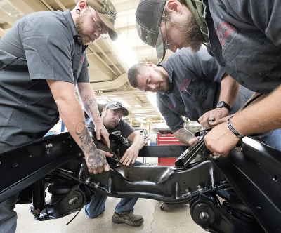 Western Iowa Tech Community College automotive technology students, from left, Devin Bravo, Eric Preston, Zach Hoover and Sterling Tronson attach brackets to the chassis of a 1966 Chevy C10 pickup truck in the shops of the Sioux City College's automotive technology department.