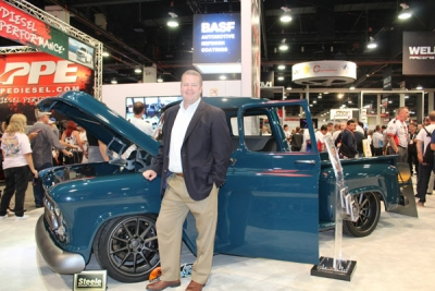 Chris Toomey, SVP of BASF Coatings, standing at the BASF Automotive Refinish Coatings booth at the SEMA Show with the 1957 Chevy Montage.