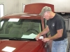 Precision Collision & Auto Glass of Frankfort co-owner Reagan Frixen matches color swatches to a Buick Lucerne.
