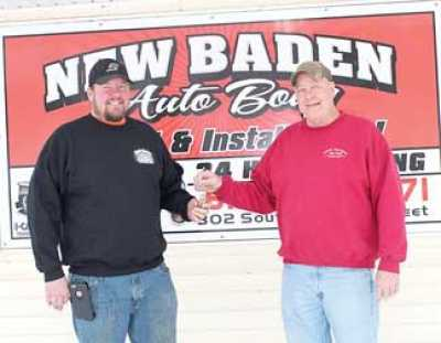 "Tim Hoerchler (right) hands over the ""keys"" of New Baden Auto Body to his son, Brian (left). Brian Hoerchler is now the third-generation owner of the family business, located at 302 S. Railway St. in New Baden."