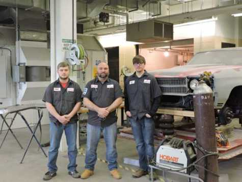 John Marshall High School students Ronnie Darrah, left, and Beryl Blake, right, stand with instructor Joe Wendt at the John Marshall Auto Body Shop after passing all four certification tests through the National Institute for Automotive Service Excellence.