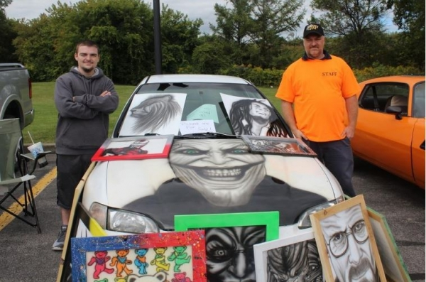 Noah Schleich (left) shows off his art on his uncle (right) Jim Schleich's car.