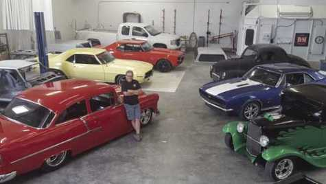 Mike Tolman, owner of Premier Collision Center in Pocatello, ID, poses in his body shop with some of the vehicles that he's renovated over the years.