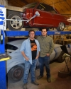 Griffith Autobody co-owners Troy Griffith and Angel Vargas stand in front of a 1960s Nova and a 1970 Camaro that are set to receive new paint jobs at the auto body shop.