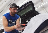 Jake Stephenson, an employee of University Collision, repairs a replacement bumper on the back of an SUV.