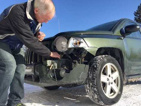 Norm Arlt, owner of Norm's Body Shop in Rogers City, MI, inspects a vehicle involved in a collision with a deer March 5. The car received about $2,400 worth of damage.