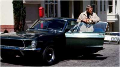 Steve McQueen (1930 - 1980) as Frank Bullit next to a Ford Mustang 390 GT 2+2 Fastback in the american crime thriller movie 'Bullitt', San Francisco, 1968.