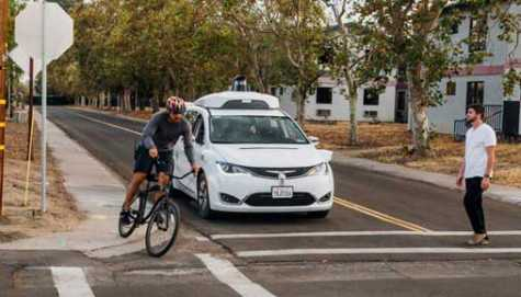 A Chrysler Pacifica minivan equipped with Waymo's self-driving car technology is tested with the company's employees as a biker and a pedestrian at Waymo's facility in Atwater, CA.