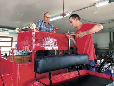 DANIEL ZOPPETTI and his father, John, at left, put some of the final touches on Florence's antique fire truck. The restored 1917-18 vehicle will be unveiled on July 9 in Florence. (Submitted photo)