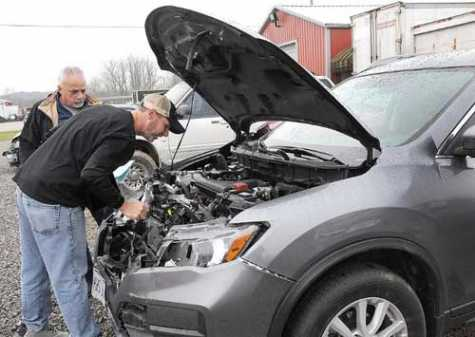 Travis Morgan, right, of B&B Body Shop and Towing, and Frank Bruno, vehicle appraiser for FrontLine Appraisals, check out the heavy damage to the front of this SUV after the driver hit a deer on Interstate 70 the weekend of Nov. 10--11.
