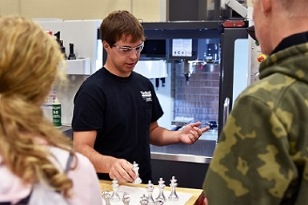 Jadon Wagner, a diversified manufacturing technology student from Winside, sets aside an aluminum chess piece crafted by the computer numerical control (CNC) machine behind him at Northeast Community College. Wagner was among Northeast students showcasing the College's Applied Technology Division during a recent Career Day for high school students.