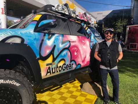"Robin Adkison, also known as ""Robin1000,"" a street artisan turned custom vehicle painter, stands with this year's AutoNation theme truck."