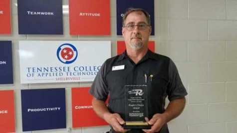 Eric Brown of Tennessee College of Applied Technology-Shelbyville holds the People's Choice Award he received during a car show held in conjunction with NACE Automechanika in Atlanta.