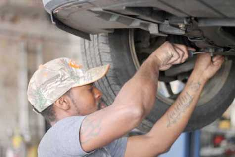 Marcus McGrier works under a car at McGrier's Auto Care in Greenwood, SC.