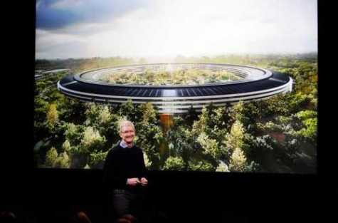 "Apple CEO Tim Cook speaks in front of a rendering of the company's new ""spaceship"" headquarters during a product launch event March 21, 2016, at Apple in Cupertino, CA. Cook said that the next time Apple does a product launch event, it will be announced at the new facility."