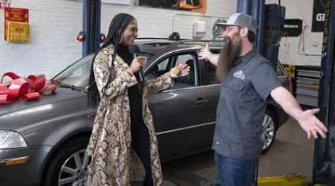 "Chimaine Brandford reacts after receiving the keys to her refurbished 2005 Volkswagen Passat from Charles Sanville, the auto repair specialist who has the YouTube channel ""The Humble Mechanic,"" on Thursday at Second Chances Garage in Frederick. CREDIT: Bill Green"