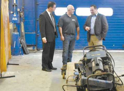 Erie 2 BOCES Associate Director Leo Fial talks with teacher Rick Drewery and Frank Todaro, owner of Collision Masters, about the recent donation.