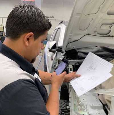 Mission Viejo Auto Collision technician Luis Cisneros reviews print out and confirms and documents weld count and location. Management then reviews and confirms communication and documentation from a mobile device or PC.
