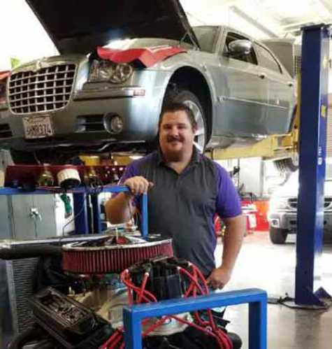 Petaluma High auto technician teacher Keith Benson with a few of his teaching tools, including a new V-8 engine and a Chrysler 300 awaiting a new engine.