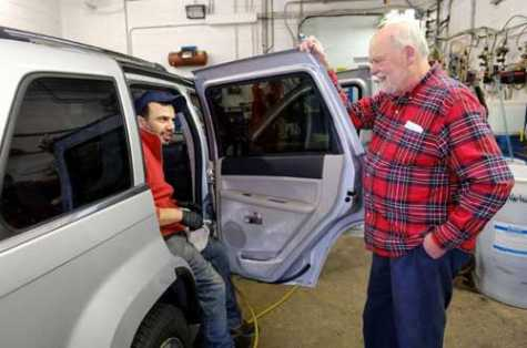 Frank Nascimento, left, talks to Alan Hartnett, right, of Hartnett Auto Body & Car Wash while detailing this vehicle inside the shop. The business closed April 4 after many decades in Danvers, MA.