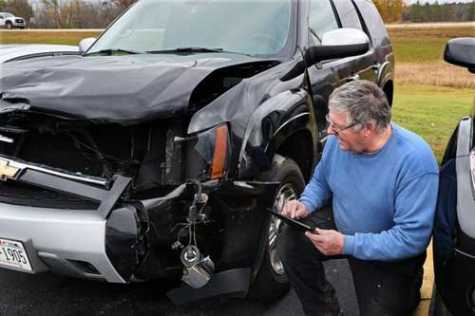 Todd Gillette, owner of Gillette's Collision Center in Waukesha, works on a repair estimate for a 2008 Chevy Tahoe. The SUV recently collided with a a white-tailed buck deer. The SUV's owner, Ryan Hunkins of Mukwonago, said his wife was driving when the buck jumped over a median barrier on I-43 and was struck by the SUV in midair.