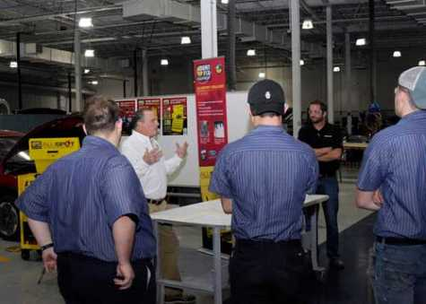 Penn College students and collision repair instructor Shaun D. Hack (in black shirt) listen as Daniel L. Maloney Jr., national sales director for Dent Fix Equipment and a member of the college's Collision Repair Advisory Committee, demonstrates a donated aluminum dent-repair station.