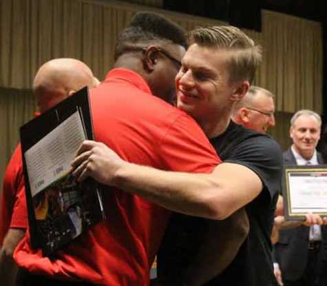 U.S. Marine Cpl. Zachary Lauterbach hugs Kevin Little, his phase one technical instructor, after officially graduating Friday from the 21st cohort of Caliber Collision's Changing Lanes program.