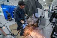 "Eddie Ruacho, a structural specialist, spot welds a vehicle with a new replacement panel in the ""cutting, fitting and welding"" department."