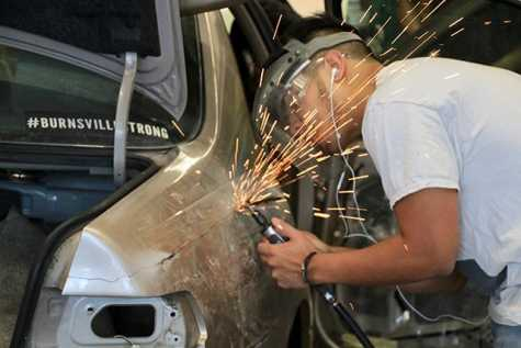 A student practices welding in an auto body class at Burnsville High School.