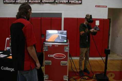 Sandpoint High School junior Cyrus Mimbs paints an imaginary car using a virtual reality paint sprayer during the North Idaho College CTE roadshow at SHS on Oct. 12.