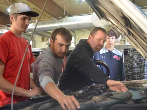 From left, Luke Claughton, Garrett Lenz, shop teacher Jason Miller and Jacob Vaughan take a look at the carburetor on a Datsun pickup at Grant Union.