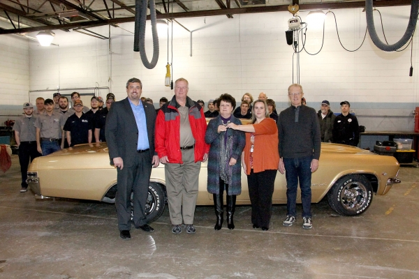 Jody Tomanek, area vice president of academic affairs at North Platte Community College, hands the keys of a 1965 Chevrolet Impala to Linda Ridenour of Brady Jan. 15. The car is the 13th classic car restoration completed by the Mid-Plains Community College Auto Tech and Auto Body Tech program. Ryan Purdy, left, Ross Ridenour and NPCC Foundation president James States are pictured, along with the students who participated in the project.