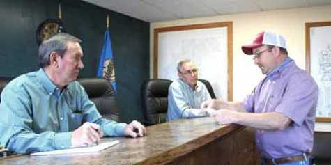 Looking over an amended executive order March 25 were, left to right, District 1 Commissioner Doug Hubbard, District 2 Commissioner Mike Brown and District 3 Commissioner Clif Hall.