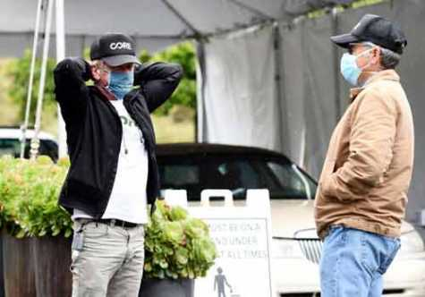 Actor Sean Penn, left, founder of the nonprofit organization Community Organized Relief Effort, talks with board member Matt O'Connell outside a CORE coronavirus testing site at Malibu City Hall on April 9 in Malibu, CA.