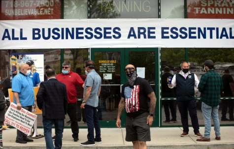 People gather May 28 in front of a Staten Island tanning salon. Owner Bobby Catone opened the salon briefly that morning in defiance of a law requiring nonessential businesses to remain closed during the coronavirus pandemic.