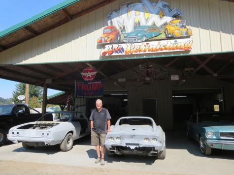 Max Childs at his shop with some of his cars.