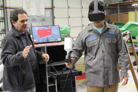 Efrain Villarreal, career and technical education automotive collision teacher, left, teaches Seth Velasco how to use the district's new virtual paint machine