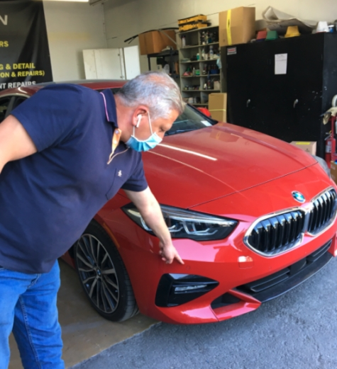 Waseem Tarashibi points out an ADAS sensor on the front bumper of a BMW at his shop, CollisionTech, in El Cajon, CA. He said such details can be easily overlooked if collision repairers don't follow manufacturers' protocols.