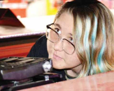 Bollman Tech Diesel student Noelle Fancher demonstrates the school's new alignment lift, part of the summer of 2019's renovations at the school. The new lift allows students to take large vehicles off the ground for inspection and work. School officials and students showed off the improvements at an Oct. 24 open house.