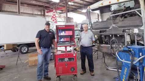 Chris Sterwerf and his father, Dennis Sterwerf, founder of Fairfield Auto and Truck Service, stand next to their shop's repair-planning computer.