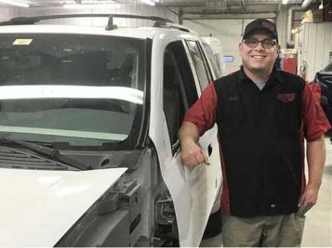 Jake Glasnovich, owner of Pete's Auto Body in Galesburg, IL, poses next to a car in the shop at 2345 Grand Ave.