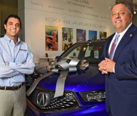Jack Hanania, Jr. (left) and father Jack Hanania stand next to a new Acura SUV in their showroom in this 2018 file photo.