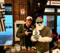 "Brandon Eckenrode, director of development for CREF, founded B-Cycled Bottles to ""upcycle"" liquor bottles into shot, rocks and tumbler glasses. Here he is at the 2020 Chicago Beer Festival with the Beer Yeti mascot."