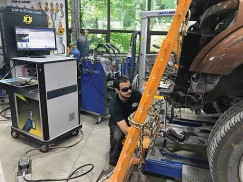 Andrew Smith at Opeka Auto Repair uses the Car-O-Tronic Vision to measure a Ford F-250 with the shop's Car-O-Liner frame machine.