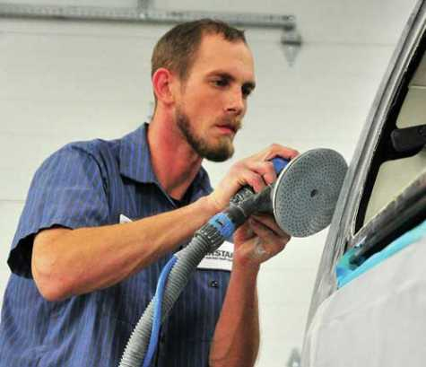 CARSTAR paint technician Devan Selanders works on a car in the body shop. Selanders has been with the company since 2011.