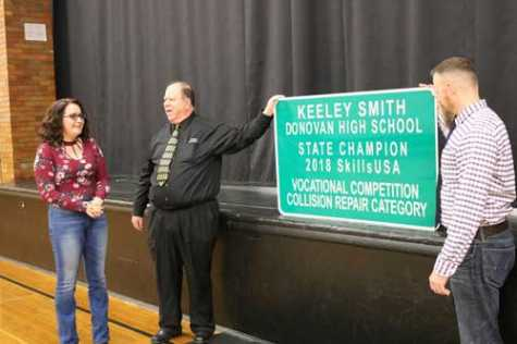 HS grad Keeley Smith is surprised by Superintendent Steve Westrick and Kankakee Area Career Center Director Matt Kelley with a highway sign recognizing her first place win in the SkillsUSA state competition.