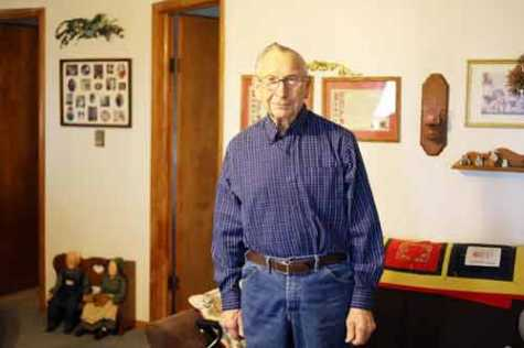 Charlie Roush, of Hopkins, MO, stands in his living room. Roush spent 65 years serving his community through auto body repair, but also in numerous other ways.